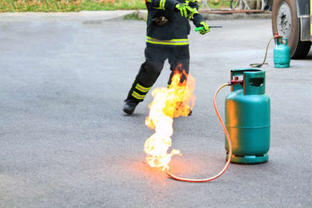 Fire burning on green gas container with Firefighter or fireman in black uniform and wheel background during fire safety training and copy space. Фото со стока