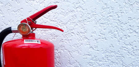 Red fire extinguisher on white rough concrete wall with copy space on right. Close up an object, Protective tool for suppressing fire.