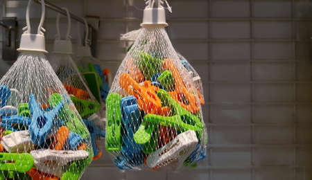 Close up colorful clothespin in net bag hanging for sale with copy space on right. Object for using dry clothes in the air.