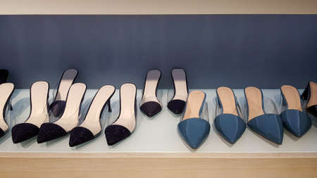 Many women's shoes on wooden shelf for sale with gray or grey wall background. Fashion for women wearing on foot.Design in casual concept Foto de archivo