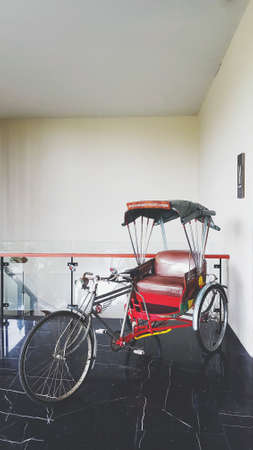 Retro tricycle bike in Thai style or rickshaw parked and show for customer in hotel with wall background in vintage tone. Asian vehicle and Type of bicycle for pick up passengers and tourist to sights