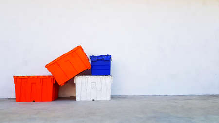 Many colorful plastic box putting and stacked on floor with white wall background and copy space