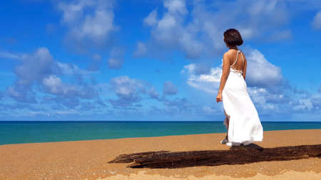 Tourist or Asian woman standing on beach wearing white dress with log or timber foreground with clear sea, white clouds and blue sky background at Mai Khao beach, Phuket, Thailand and copy space.