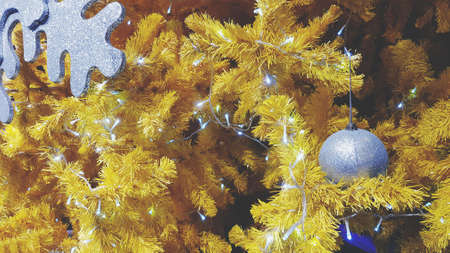 Silver ball and white lighting decorated on yellow pine tree in vintage tone. Happy new year, Christmas and Winter festival concept 版權商用圖片