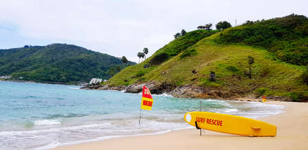 Yellow surfboard of rescue or guard on beach with yellow and red flag to tell people or tourist can swim on sea in this area only with green mountain and sky background. Beauty in nature with ocean. 版權商用圖片