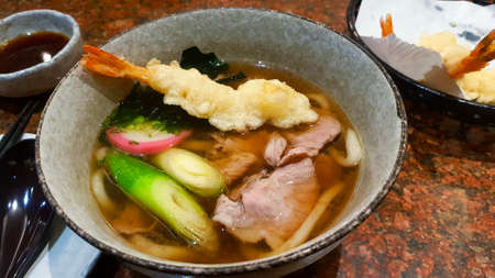 Udon noodle with soup, sliced pork, seaweed or alga, Japanese spring onion and tempura on bowl at Japanese restaurant. Hot or Asian food.