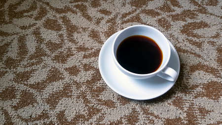 Top view of white cup of black coffee on brown rug or carpet background with copy space. Flat lay of hot drinking on cotton floor wallpaper.