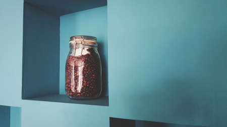 Glass bottle of coffee seed putting on green wooden self and wall background for sale or decorated at café shop in vintage tone with copy space on right. 版權商用圖片