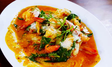 Close up Shrimp on dry red curry with sliced red chili, kaffir lime leaves, basil and herb ingredient on white dish or plate at restaurant. Thai Spicy food 版權商用圖片