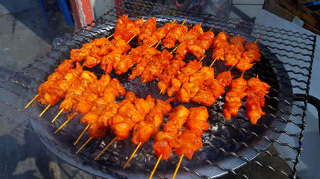 Grilled red chicken, beef or pork charcoal stove on local street food in Thailand. Barbeque in Thai style. Cooking Asian food. Delicious meal and taste sweet with ingredient and spices or pimento 版權商用圖片