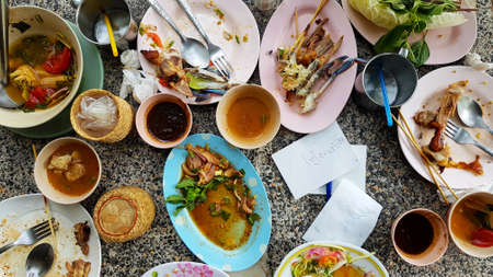 Flat lay of Thai food with spicy papaya salad, white noodles, bone chicken, crab salad, sauce and fresh tomato remain on table after eat lunch at restaurant. Food waste concept. 版權商用圖片