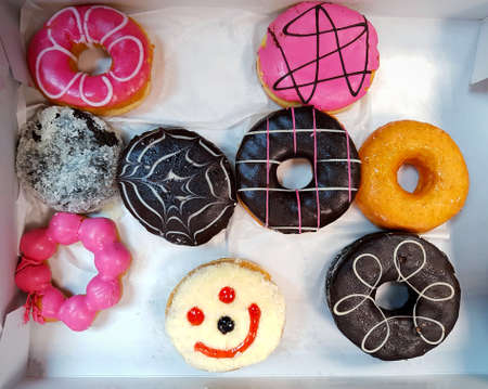 Top view of colorful donut on white paper background. Flat lay of dessert contains in box. Food design and unhealthy or junk food concept. 版權商用圖片