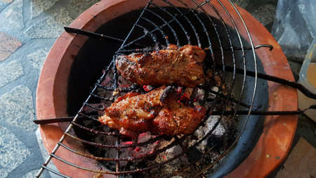 Two pieces of Grilled pork bone rib, beef or chicken charcoal stove. Barbeque in Thai style. Cooking Asian food to eat at camping time. Delicious meal and tasty