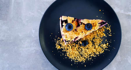 Top view of Blueberry crumble on black dish or plate on gray concrete background with copy space on left. Flat lay of dessert on grey table at café shop. Food handmade with fruit and Fine crackers. 版權商用圖片