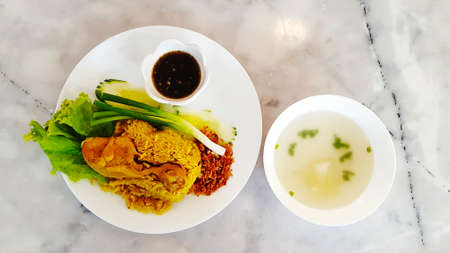 Top view of Chicken Biryani with black sweet sauce, dry onion, fresh green cabbage, cucumber,  spring onions on white dish and soup on bowl on marble table with copy space. Flat lay of Asian food.