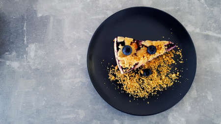 Top view of Blueberry crumble on black dish or plate on gray concrete background with copy space on left. Flat lay of dessert on grey table at café shop. Food handmade with fruit and crackers topping.