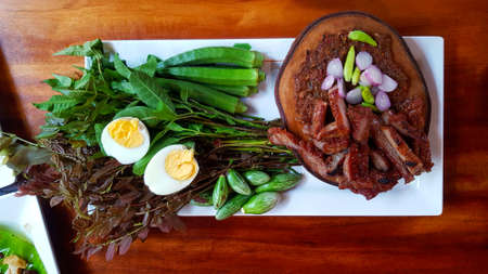 Top view of Thai local food with fried or grilled pork, fermented fish, red onions and green chili on wooden cutting board, boiled egg and fresh vegetable on white plate or dish. Spicy Asian food 版權商用圖片