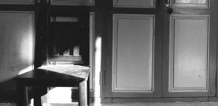 Wooden chair with shade of sunlight on vintage or classic door in black and white or monochrome tone. Retro object with light in morning.