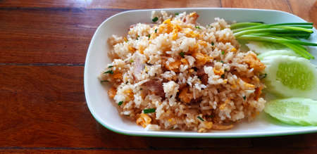 Thai fried rice with pork, fresh vegetable , slices of cucumber and spring onions on white plate or dish on wooden table with copy space on left at Thai food restaurant. Asian food for lunch.