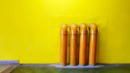 Four yellow water pipeline on yellow concrete wall for background with copy space. Oil pipe installed on floor.