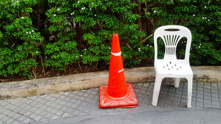 Orange traffic cone and white plastic chair are on footpath with white flower and green plant or tree background at garden with copy space. Seat with traffic sing object.