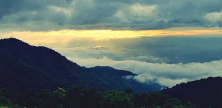 Beautiful landscape view of green mountain with forest, mist or foggy and sunlight in morning at Phetchabun province, Thailand. Cloudscape on hills on new day. Landmark for travel and Good air fresh.