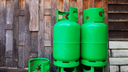 Green gas tanks on wooden wall or wallpaper with copy space on left. Group of object to make fire for cooking food in kitchen. Energy or Dangerous equipment keep away from heat or open flame and fire.