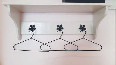 Three clothes or coat hanger hanging on white wall with wooden shelf on top. Group of object and design