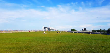 People sitting and relaxing on the green grass field roof of building with blue sky and white cloud near marina barrage at Singapore, Singapore. Beauty of nature and Relaxing time. Landmark for travel