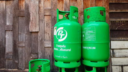 Bangkok, Thailand - March 5, 2021: Green gas tanks on wooden wall or wallpaper with copy space on left. Group of object to make fire for cooking food in kitchen. Energy or Dangerous equipment.