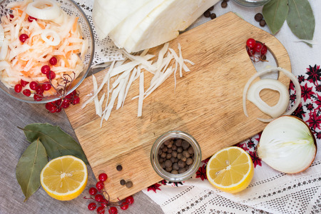 pickle: Bowl with sauerkraut and pickle ingredients on chopping board Stock Photo