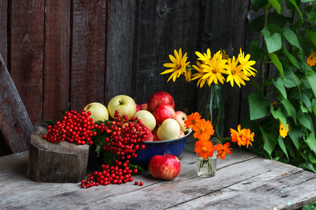Apples, berries and flowers on a wooden table