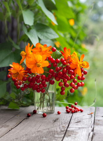Bunch of flowers and berries in a glass
