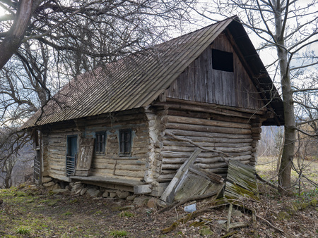 Log house. Old single house. Photo of an unusual house in the forest. Abandoned single small house in mountain