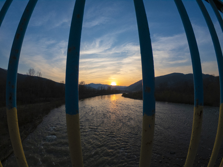 sunset over the river view from the bridge over the river in the mountains