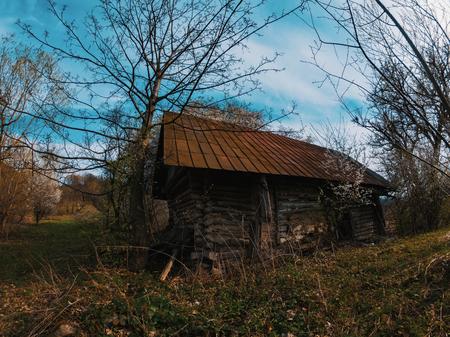 La vecchia casetta di legno fatiscente del paesaggio pittorico si trova da sola nella radura Archivio Fotografico