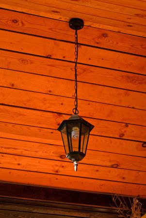 Lamp hung up by chain on wooden background