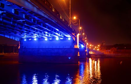 Bridge with blue and red lights at night