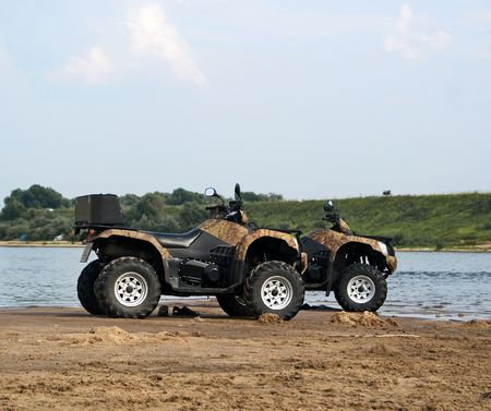 A pair of quad bikes on sandy riverside