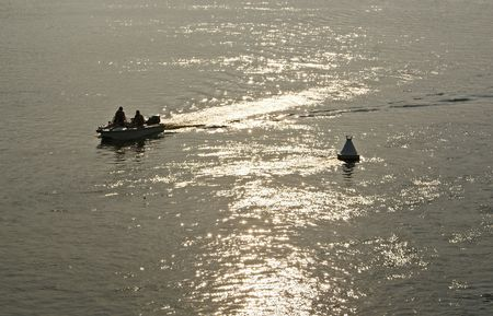 People riding a motor boat along the river near white buoy at sunset  Stock Photo