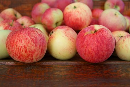 Red apples laying on wooden bench