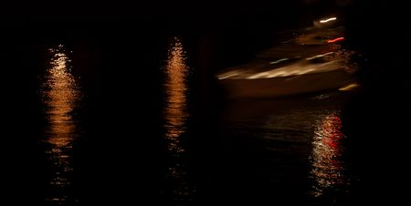 Light reflection in water at night, yacht in blur motion Stock Photo