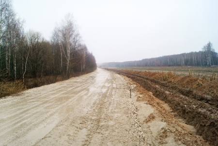 Dirty gravel road in the country-side in early spring Stock Photo