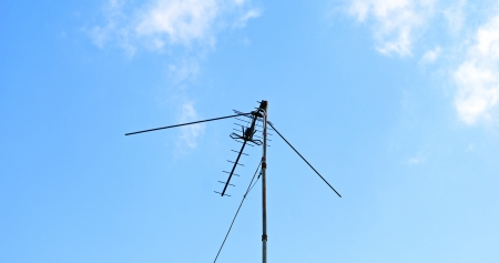 External outdoor TV antenna with amplifier in the blue sky