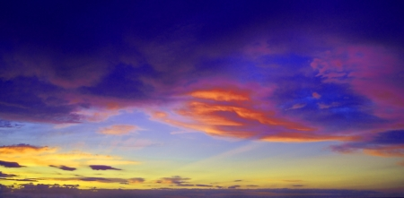 Saturated colorfull clouds with sun rays at sunset Stock Photo