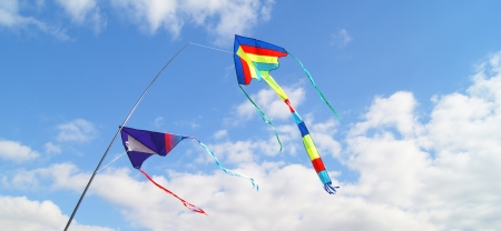 Two kites flying high in the sky