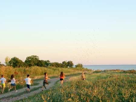 A group of children running to the sea at sunset with a firecracker in the sky