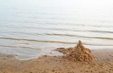 Heap of clean sand shaped as a castle on sea beach