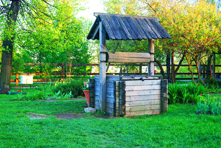 Old wooden draw well in the garden near apiary Stock Photo