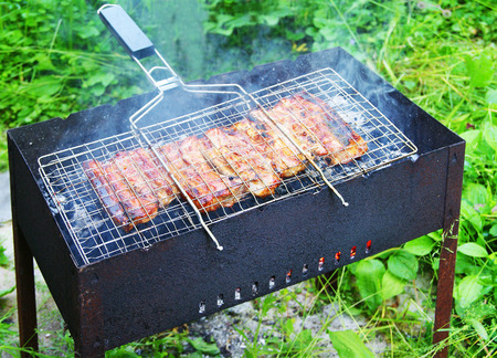 Barbecue stand with grilled pork ribs on metal grid over open fire